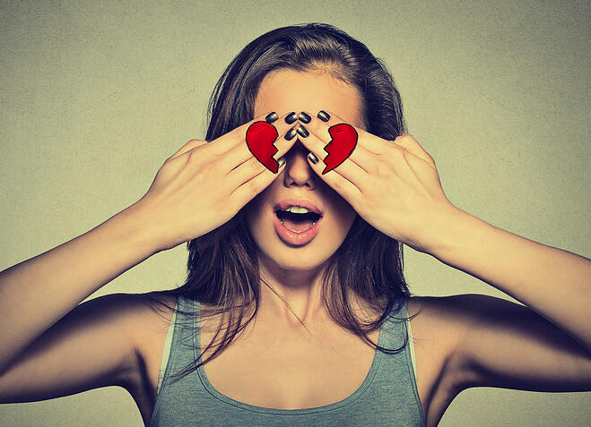 Beautiful young woman eyes covered by hands with broken heart printed on them. Girl in love isolated on gray wall background